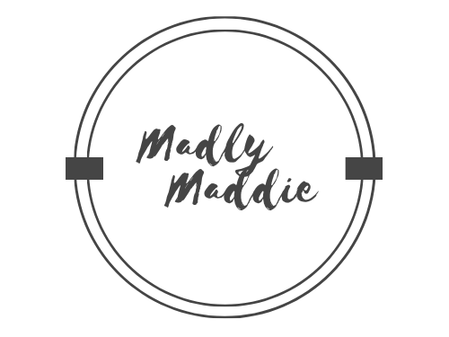 """The Madly Maddie logo. It is one large circle with a smaller circle inside. They are connected by two black rectangles on both the left and right sides of the circles. The words """"Madly Maddie"""" are in the middle."""